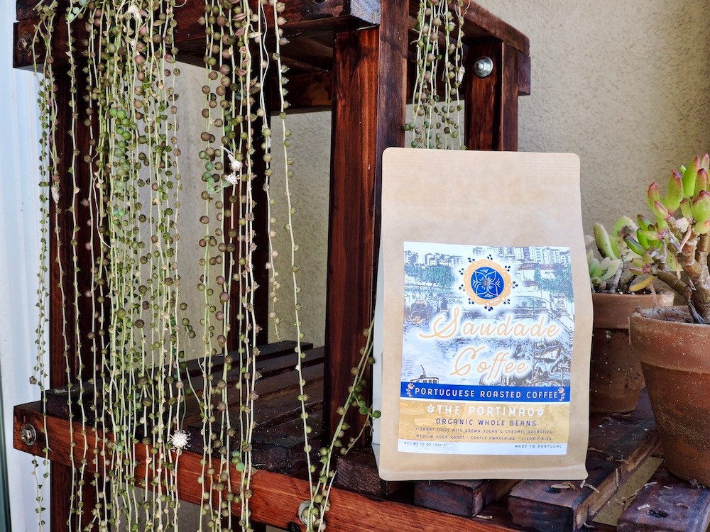 A bag of Saudade Coffee sits on a a wooden shelf with plants