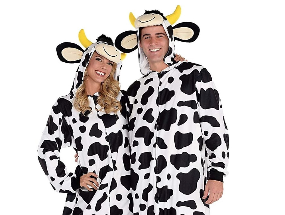 Two adults wear cow onesie costumes