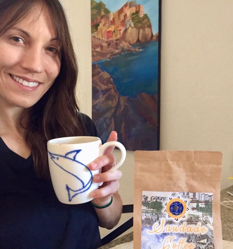 Girl holds cup of coffee next to bag of Saudade Coffee