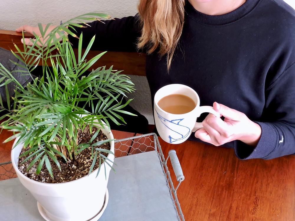Girl sits at wooden table with a cup of coffee in hand