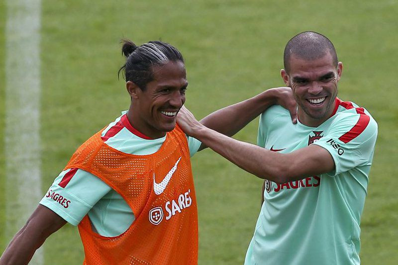 Bruno Alves and Pepe helping each other with stretches on the field