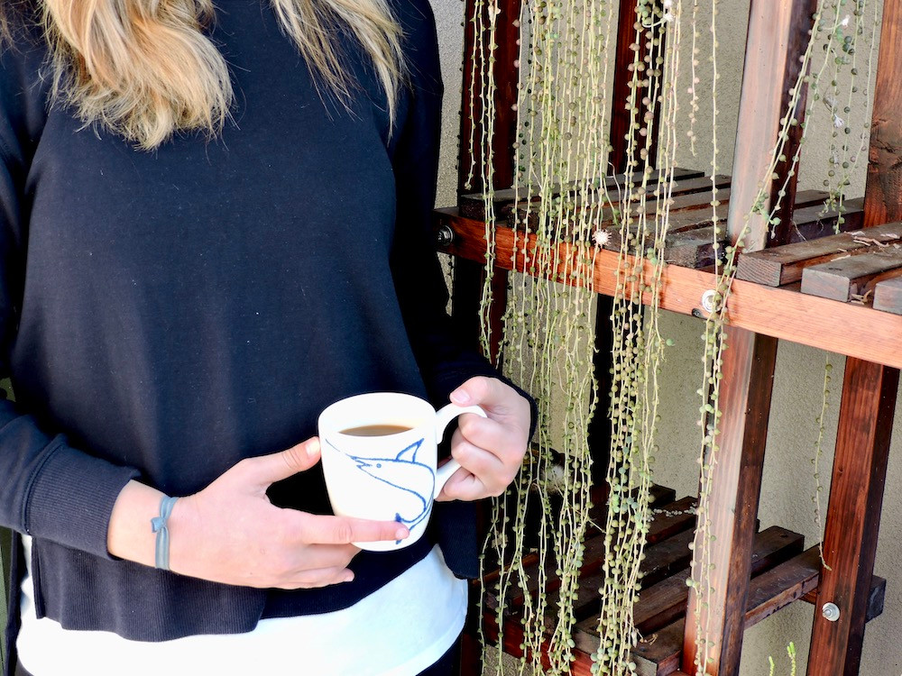 Girl stands near plant stand holding cup of Saudade Coffee