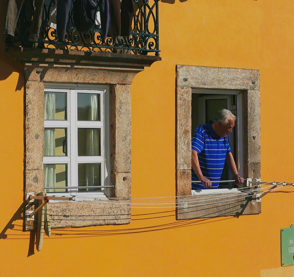 A man looks out his window in Portugal