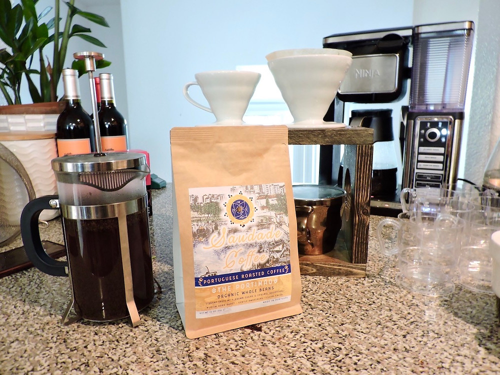 A bag of Saudade Coffee sits near a french press, pour over coffee maker, and a coffee pot