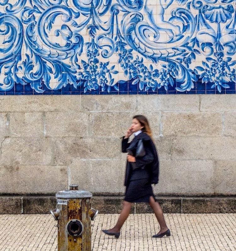 A Portuguese university student walks down a street in Porto, Portugal