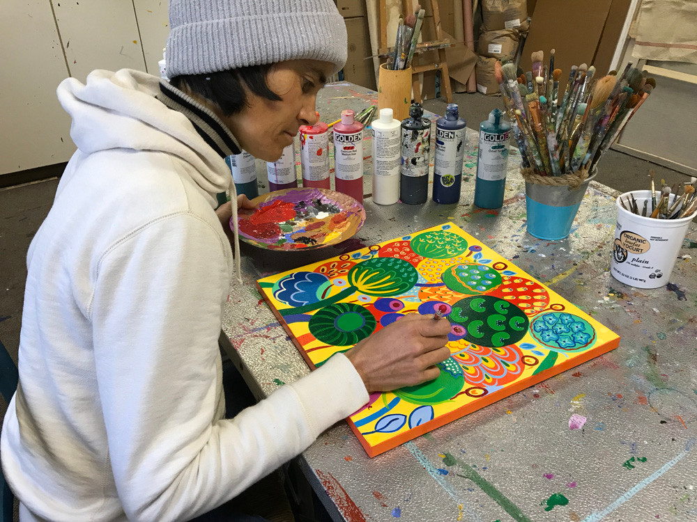 portrait of artist flo de bretagne at work on one of her seeds paintings