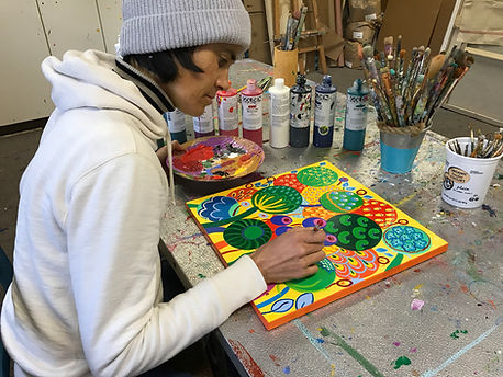 Flo de bretagne is painting ona small artwork representing colorful seeds and flowers.