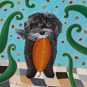 colorful portrait of a black labradoodle holding an automn leaf in his mouth and standing ona blanket with bownish square patterns in front of a turquoise wall with more automn leaves