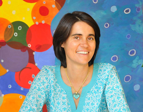 Picture of artist Flo de Bretagne in front of one of her colorful bubble paintings