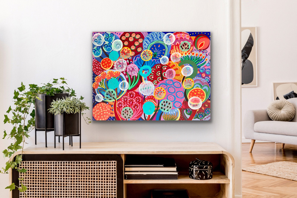 a small rectangle painting representing colorful seeds and flowers hangs above a wooden furniture with indoor plants