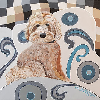 square portrait of a labradoodle seating on a comfy pillow