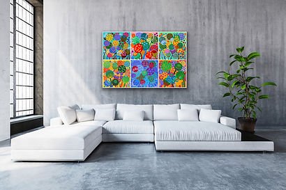 6 little square paintings representing flowers are hanging together above a very large white sofa next to a high window