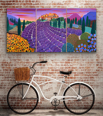 a white bike and a large triptych painting are against a brick wall. The painting represents French Provence with tens of lavender bushes and sunflowers