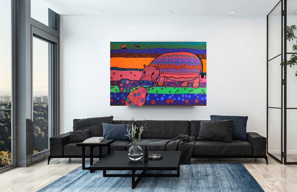 A large painting with vibrant colors depicting a mama hippo kissing her two youngsters, hang above a black leather couch