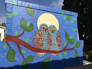 a mural at a private home representing two owls in love in front of a full moon