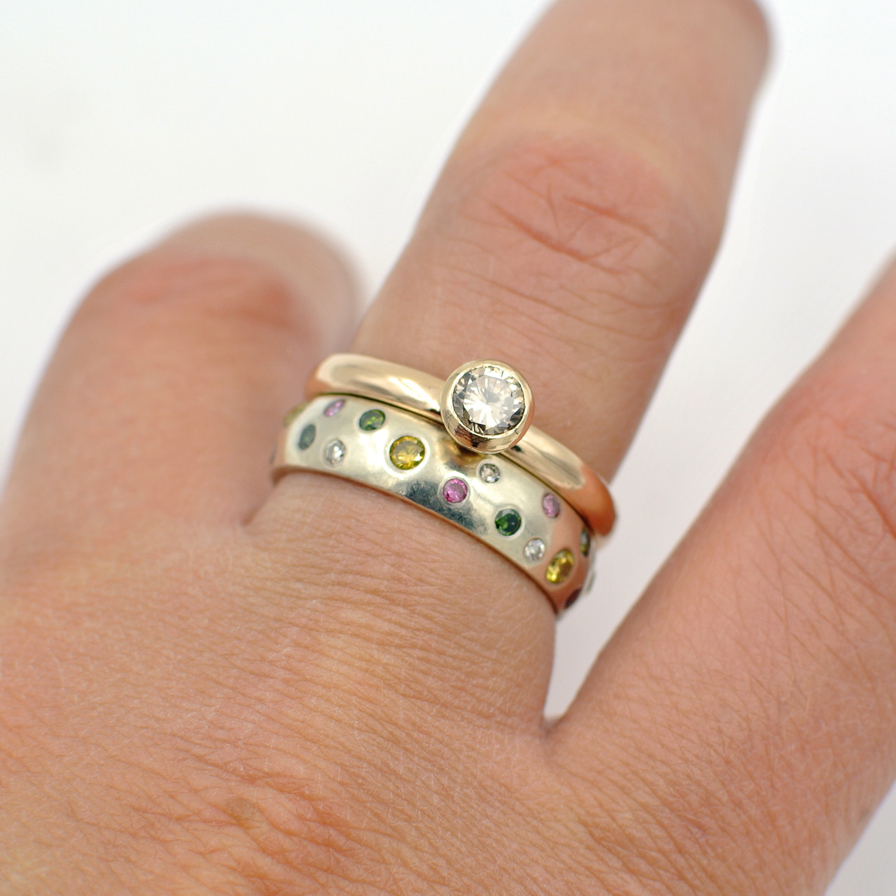 A finished remodelled diamond ring sat next to a bright and colourful diamond eternity ring.