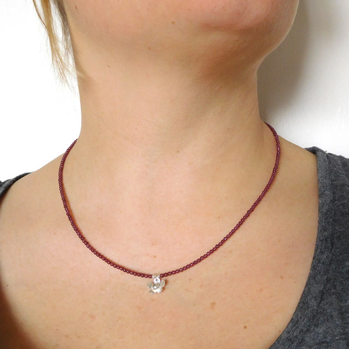 A handmade sterling silver pendant and garnet beads. Perfect gift for someone special