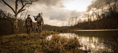 Bowhunters by a Pond