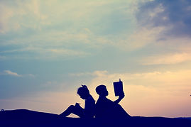 Silhouette of happy boy and girl reading