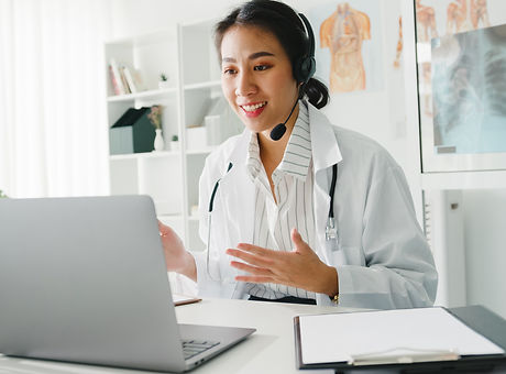 Young Asia lady doctor in white medical uniform with stethoscope using computer laptop tal