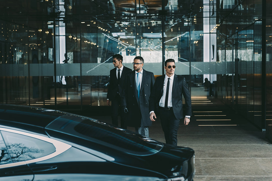 businessman and two bodyguards walking to car.jpg