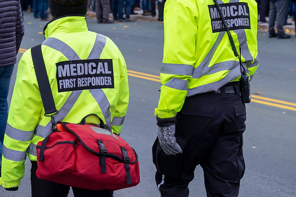 Two medical responders walking in a street with bright yellow coats with the words medical