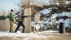 Instructor on shooting range teaches his student tactical gun shooting behind and around c