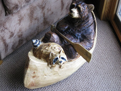 Chainsaw carved bear in canoe