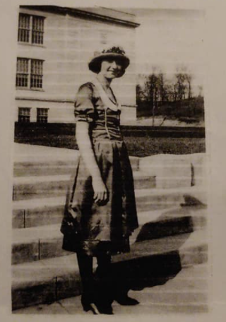 A woman in a dress, heels, and hat with cropped hairstyle in the mid-1920s
