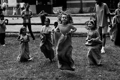Children sack race with smiles on their faces.
