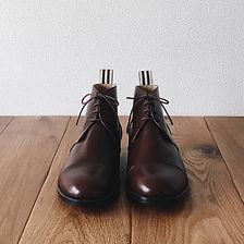チャッカー ブーツ(Chukka boots)。この靴は伝統的なハンドソーンウェルテッド製法でえ作られています。ハンドソーンウェルテッド製法とは・・・靴作りが機械化される以前、数百年も前から伝わる手縫い靴の代表的な製法で、アッパーとソールの取り付けを100%手縫いで行います。現在は、手間と時間と材料費が高価な事から既製靴が店頭に並ぶ事は稀で、高級フルオーダーの靴である事が多い製法です。 中底が厚く、しっかりとしていて構造的にも頑丈で安定感があり型くずれせず、何度でもソール交換が可能なこの製法は、何度も修理して履くのが当たり前だった時代から修理がしやすい作りになっています。ビスポーク、オーダーネイド、誂え靴
