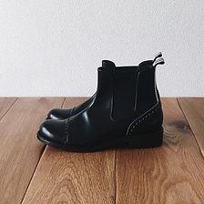 チェルシーブーツ(Chelsea boots)。この靴は伝統的なハンドソーンウェルテッド製法でえ作られています。ハンドソーンウェルテッド製法とは・・・靴作りが機械化される以前、数百年も前から伝わる手縫い靴の代表的な製法で、アッパーとソールの取り付けを100%手縫いで行います。現在は、手間と時間と材料費が高価な事から既製靴が店頭に並ぶ事は稀で、高級フルオーダーの靴である事が多い製法です。 中底が厚く、しっかりとしていて構造的にも頑丈で安定感があり型くずれせず、何度でもソール交換が可能なこの製法は、何度も修理して履くのが当たり前だった時代から修理がしやすい作りになっています。ビスポーク、オーダーネイド、誂え靴