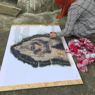 Detail of Arya writing on the artwork - 2018 Refugee Stories  PhotoEast Festival © Gillian Allard