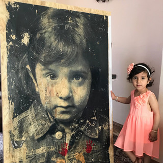 Mina at home  with her wooden portrait.  Refugee Stories  PhotoEast Festival 2018 © Gillian Allard This image was taken as a publicity photo for the project.  Mina had just added her tiny hand and foot prints to the bottom of the image in red and gold paint.