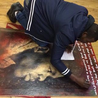 Detail of teenage Sudanese boys writing on the portrait of his friend 2018 Refugee Stories  PhotoEast Festival © Gillian Allard