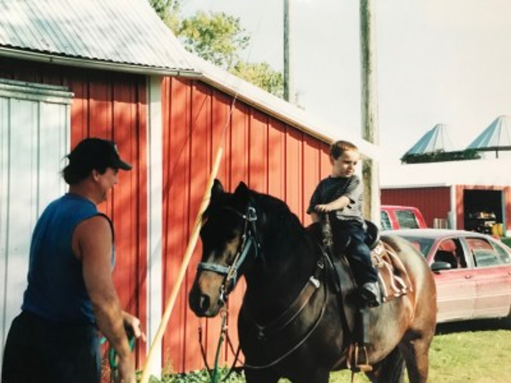 My dad teaching me to ride a horse.