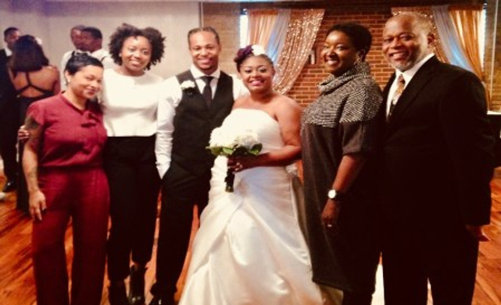 On my wedding day in 2016, with my wife Charity and some other family members.