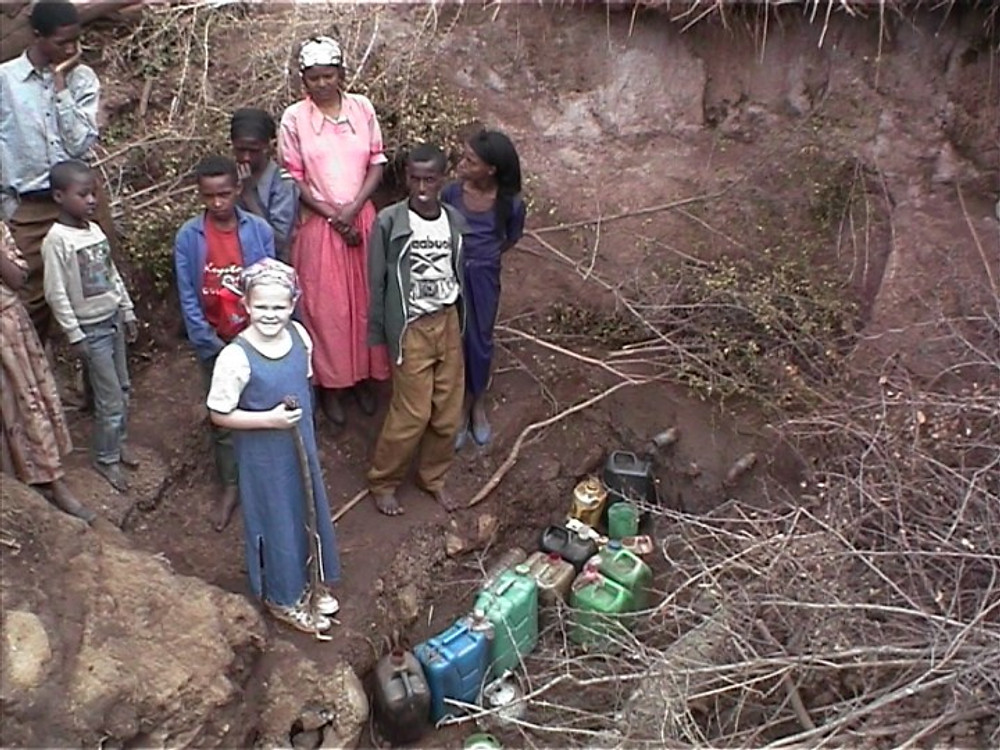 Me (in a blue dress) with other villagers on a water site in Ethiopia.