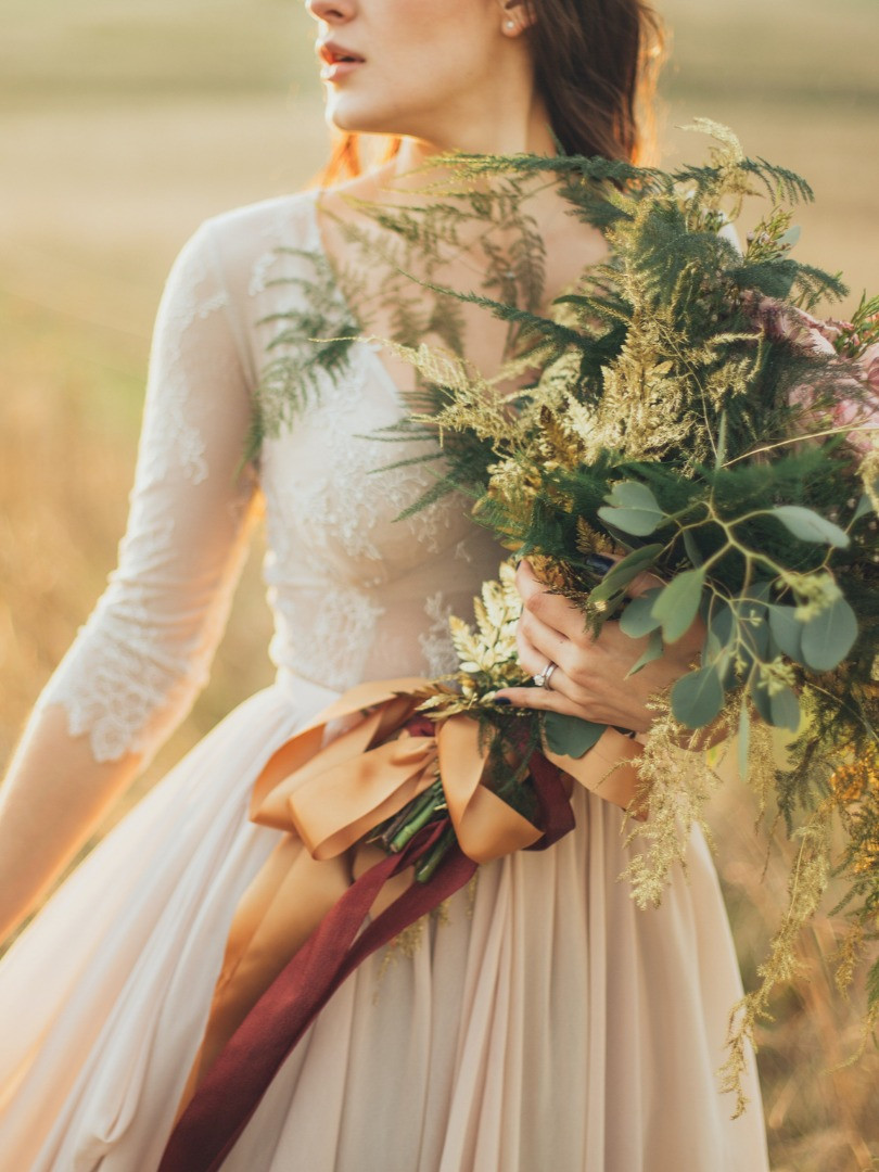 Casual bride with wild flower bouquet at sunset