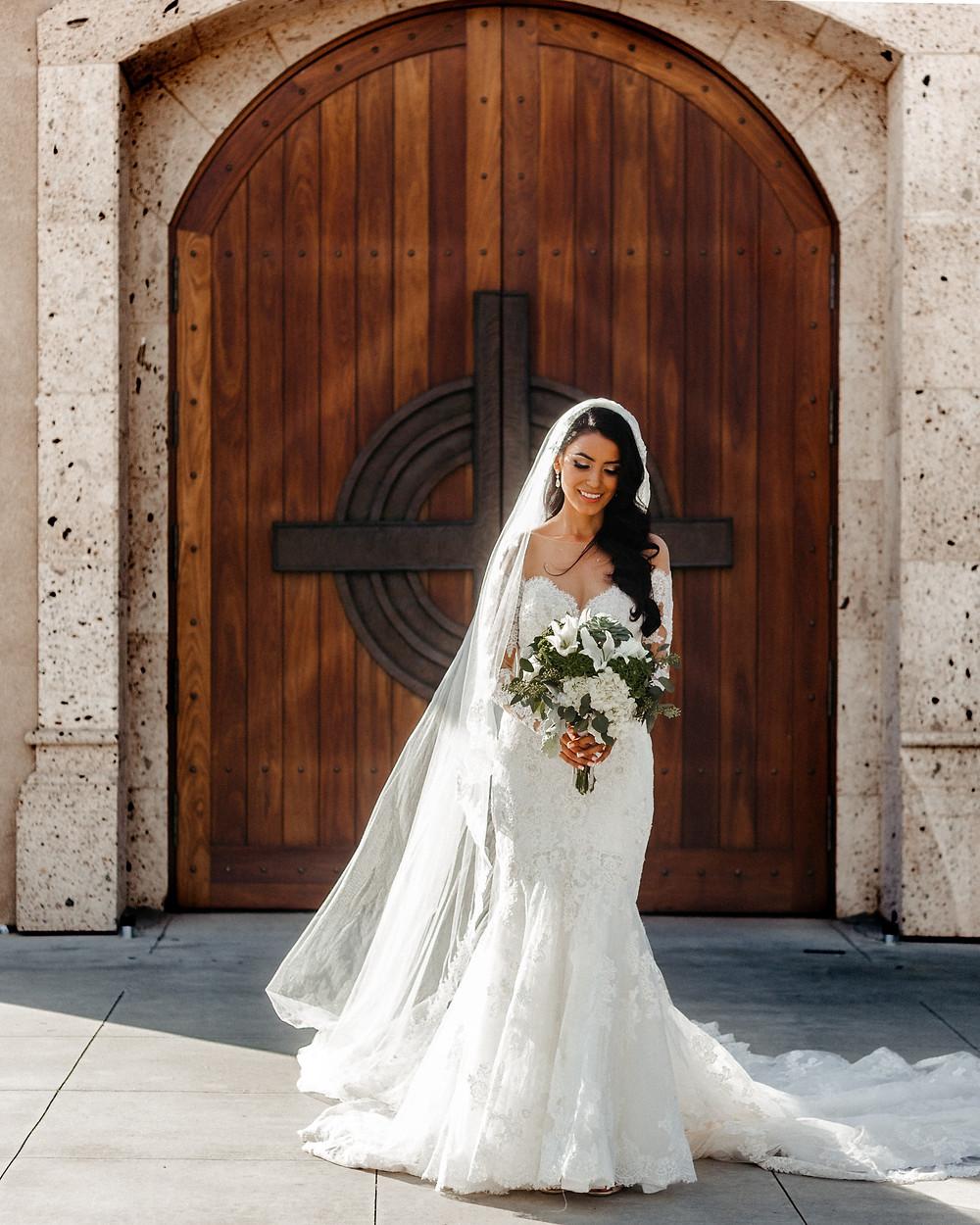 Bride holding a bouquet outside a church