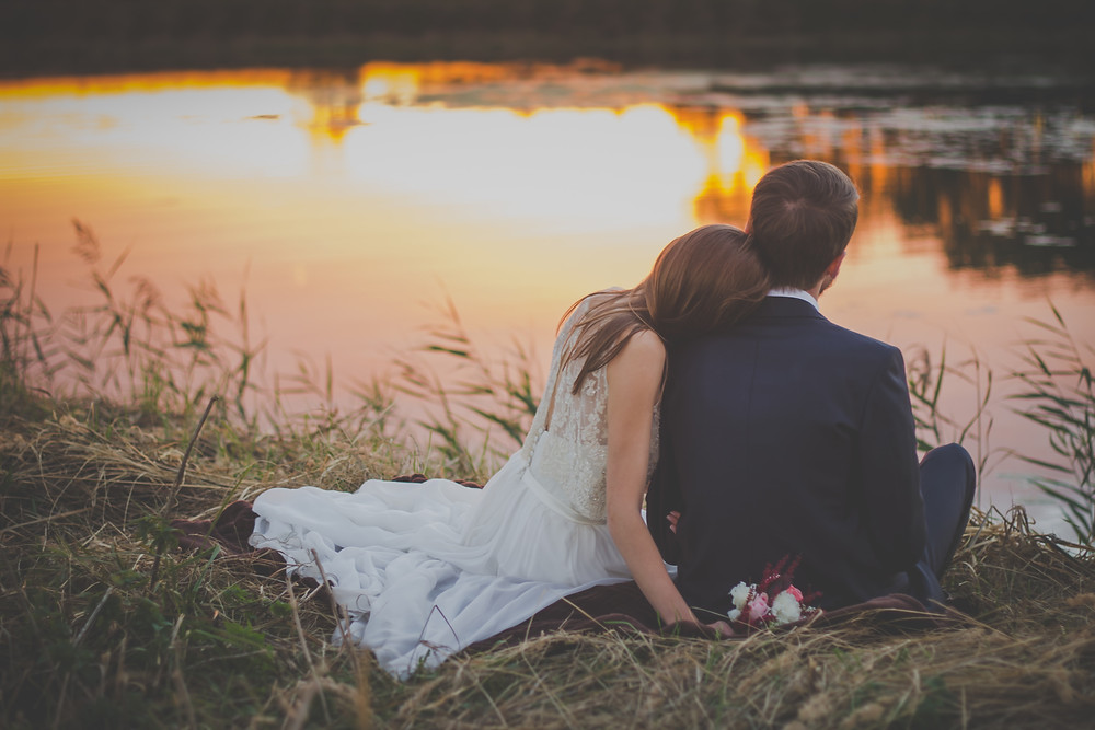 Intimate bride and groom sitting infront of a sunset