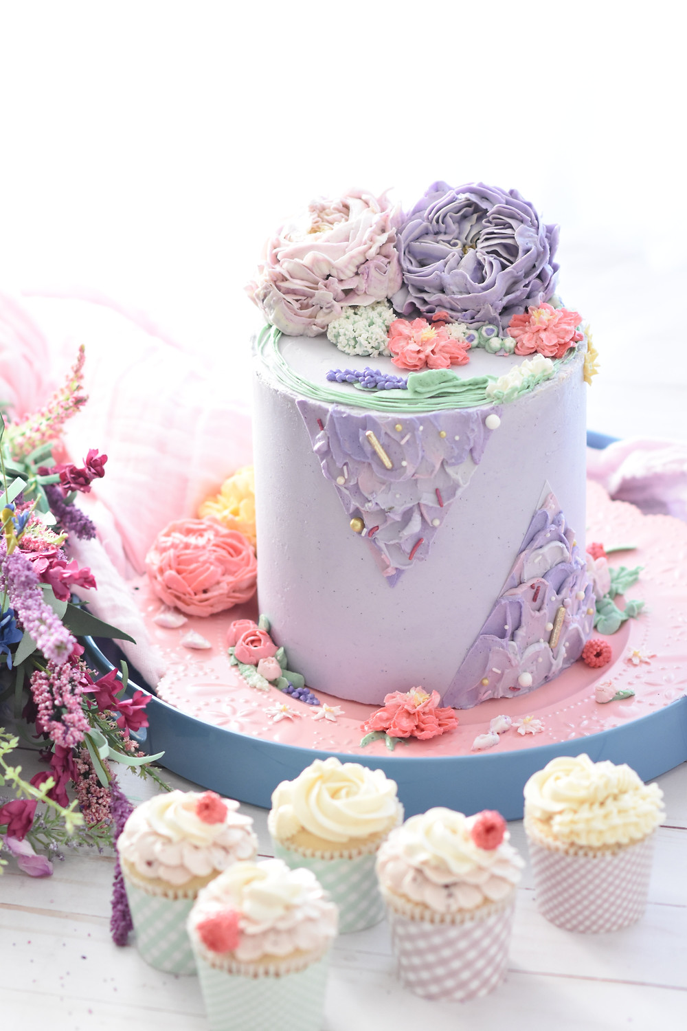 Baby shower lilac cake with flowers and cupcakes