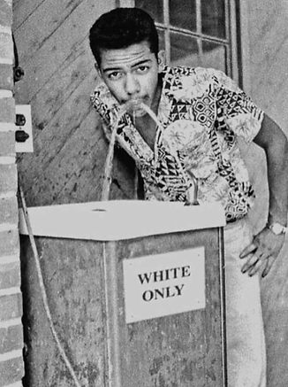 Black man drinking from a white only fountain