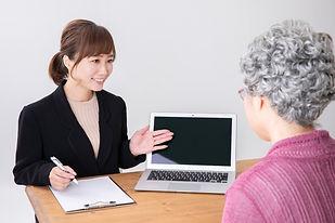 老齢の女性に説明する女性スタッフ