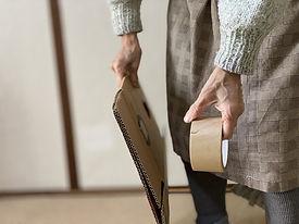 段ボール紙とテープを持つ老齢の女性