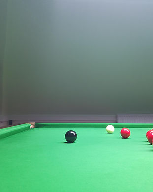A snooker table with reds an black ball.