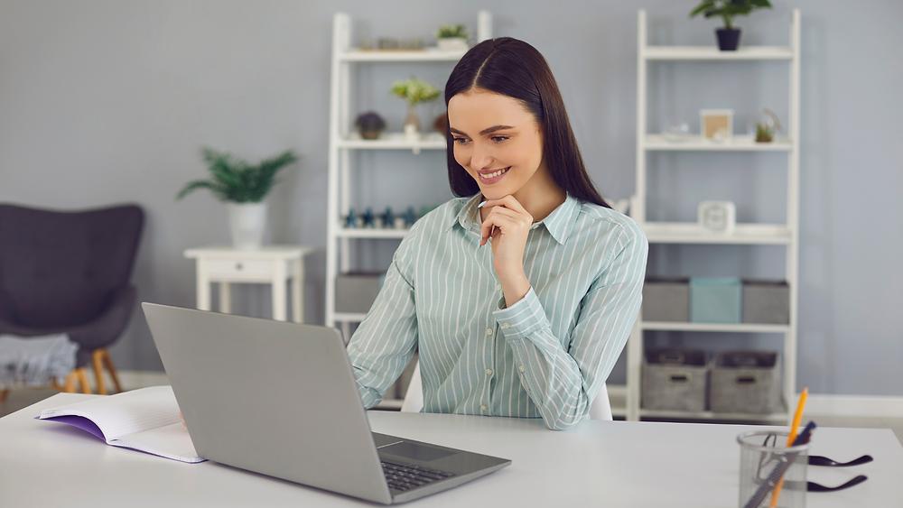 Mulher sorridente olha para a tela do notebook