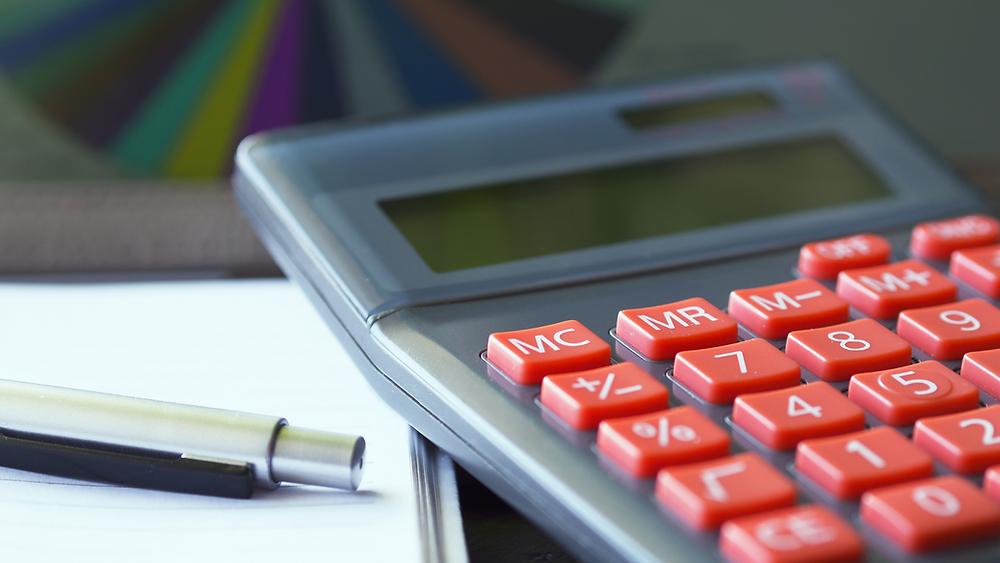 foto de uma calculadora ao lado de uma caneta em cima de um caderno