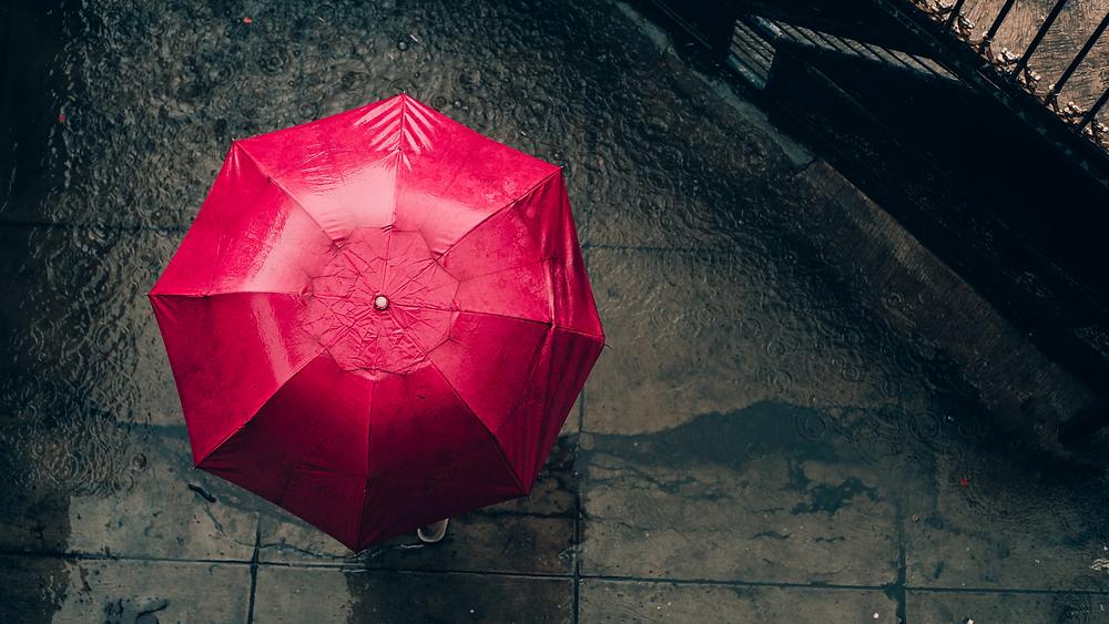 Na imagem temos um guarda-chuva vermelho aberto durante uma tempestade