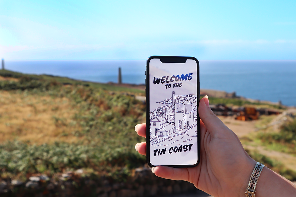A hand holds a mobile phone showing the XplorTINCOAST landing page. There's a sunny coastal view in the background.